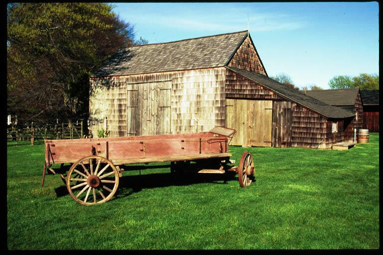A wagon in front of a wooden building on Mulford Farm