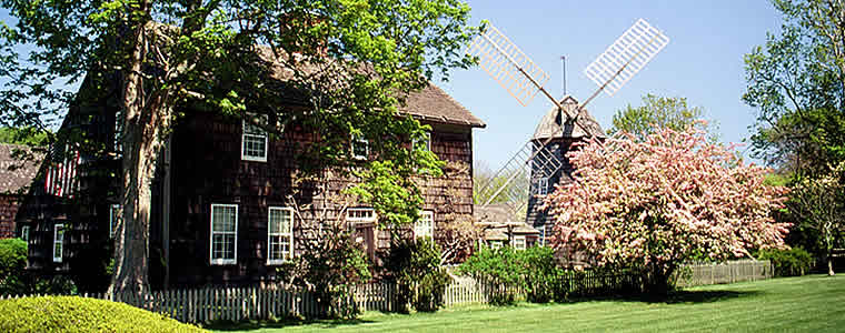 A wooden house next to a windmill with trees surrounding both