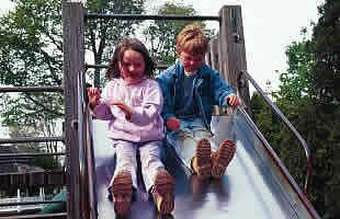 Two kids sliding down a slide